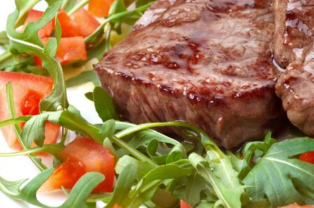 juicy fried beef steak with roocket salad and sliced tomatoes photo