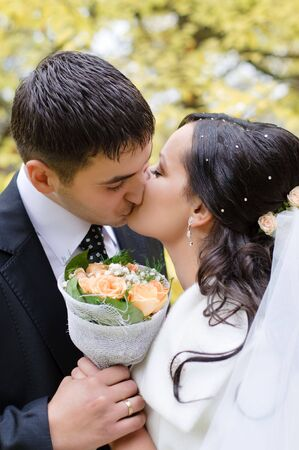 young just married couple kissing in the park photo