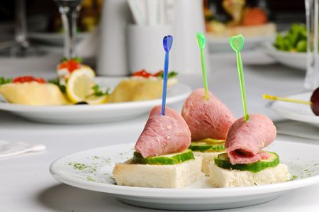three meat and cucumber canapes with toothpick photo