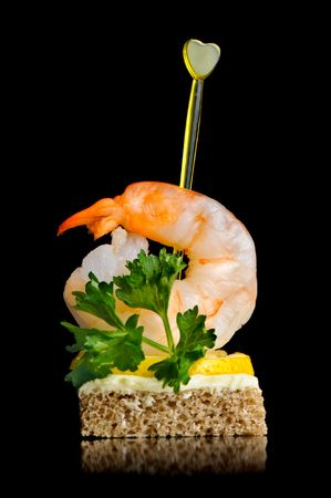 delicious canape with boiled shrimp, isolated on black photo