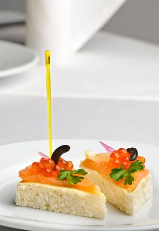 canape with red caviar and smoked salmon, served on plate photo