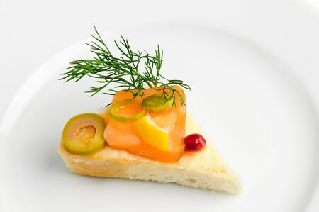 dill seed: canape with slice of smoked salmon, green olive, dill and seed of pomegranate Stock Photo