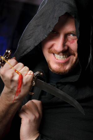 medieval looking menacng man with dagger wearing black cloak with hood Stock Photo - 4054752