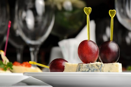 canape with Roquefort cheese and grape berry, served at restaurant table photo