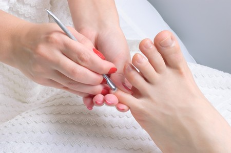 body care series. pedicure applying - toe nails cleaning and moisturizing with special solution. photo