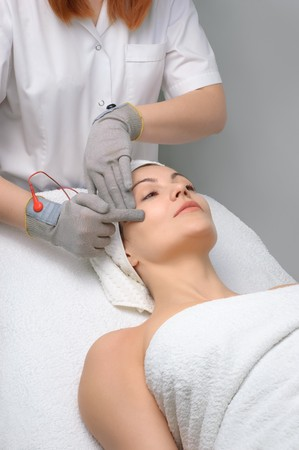 woman getting special electric facial massage in the beauty salon photo