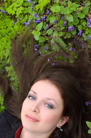beautiful blue-eyed brunette girl lying at green spring meadow photo
