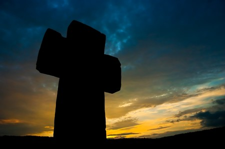 awe: stone cross silhouette at the background of the awe evening sunset sky Stock Photo