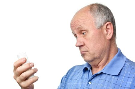 senior bald man is examining something in his hand photo