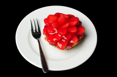strawberry cake lying on white dish isolated on black photo