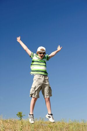 happy teenage boy jumping  on the hill photo