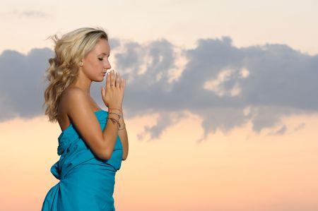 jonge blonde meisje bidden buitenshuis avond op tijd