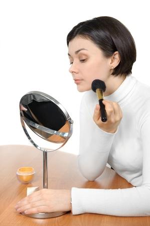 brown  eyed: young brown eyed lady applying powder using soft brush
