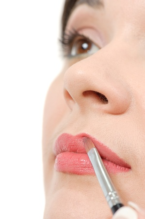 nose close up: applying liquid glossy lipstick using special brush Stock Photo