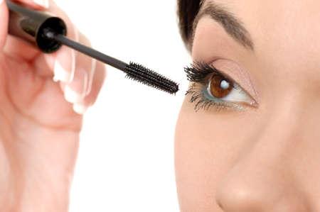 brown  eyed: young brown eyed lady applying mascara using lash brush