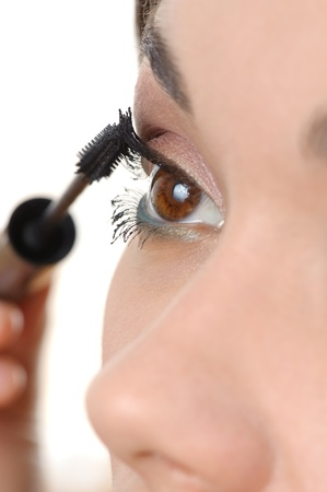 closeup of young brown eyed lady applying mascara using lash brush photo