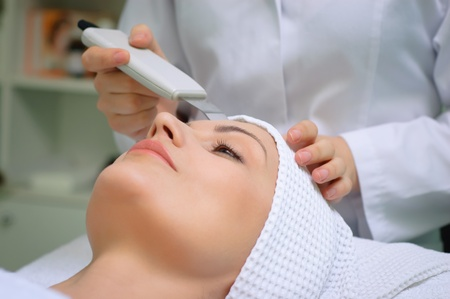 beauty treatment clinic: woman getting ultrasound skin cleaning at beauty salon Stock Photo