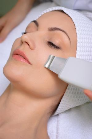 pulizia viso: donna che si pelle pulizia ad ultrasuoni al salone di bellezza