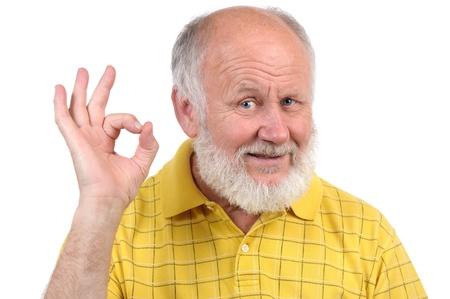 senior grappige kale man in geel t-shirt is shows gebaren en grimassen
