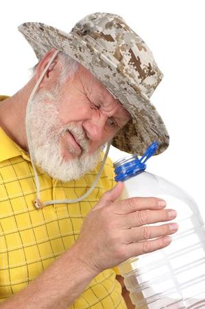 senior balding bearded man holding empty plastic bottle photo