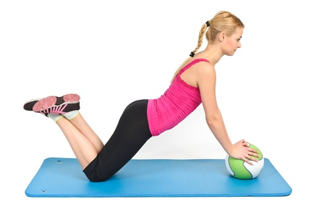 Jonge blonde vrouw doet push-ups op de geneeskunde bal