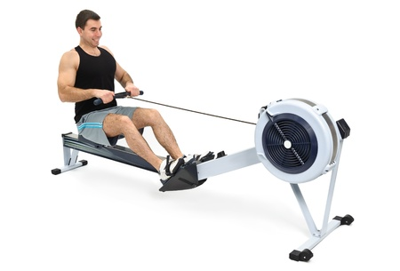 exercise machine: man exercising on rowing machine,  hands slightly blurred in motion