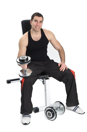 young man posing with dumbbells sitting on bench, on white background photo