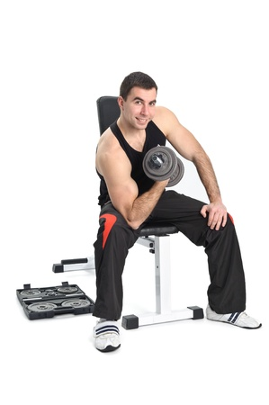 young man posing with dumbbell sitting on bench, on white background