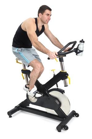 een man doet indoor fietsen oefening, op een witte achtergrond Stockfoto