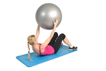 laying abs exercise: Female lying abs crunching exercise with fitness ball. position 2 of 2. Stock Photo