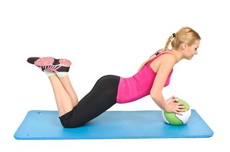 Mujer rubia joven haciendo flexiones en la bola de medicina, la posici�n m�s baja
