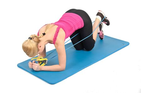 Young blond girl doing kneeling butt blaster exercise using rubber resistance band. position 1 of 2. photo