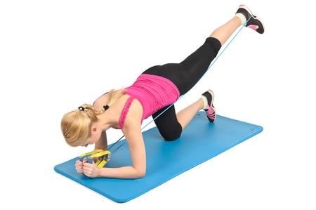 Jong blond meisje doet knielen butt blaster oefening met behulp van rubberen weerstand band. 2-positie 2.