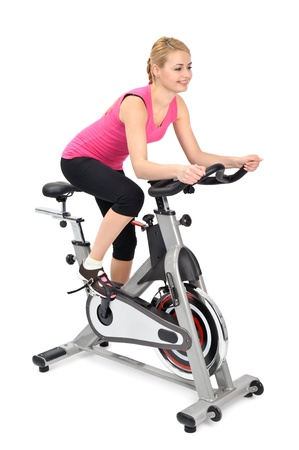 mujer joven haciendo ejercicio en bicicleta bajo techo, en el fondo blanco Foto de archivo