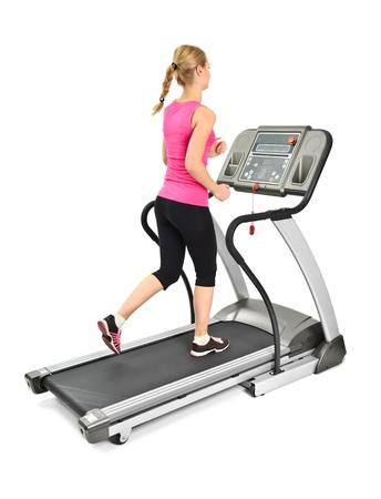 mladá žena dělá cvičení na běžeckém pásu, na bílém pozadí, nějaký rozmazaný pohyb Reklamní fotografie