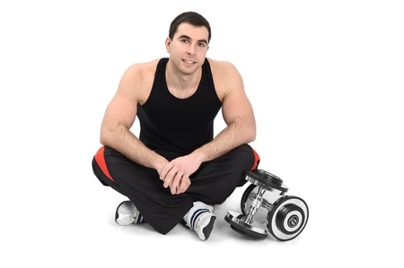 young man posing with dumbbell sitting on floor, on white background Stock Photo - 12234621