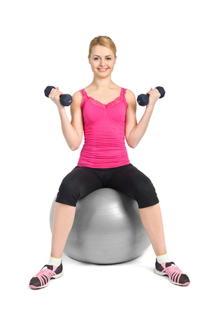 young woman posing with dumbbells sitting on fitness ball, on white background Stock Photo - 12234625
