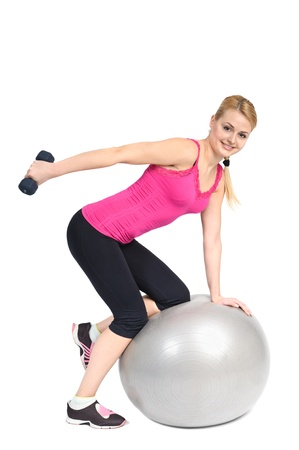 Young woman doing Standing Bent-Over Dumbbell Triceps Extension on Fitness Ball, phase 2 of 2. Stock Photo - 12234628