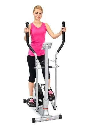 jonge vrouw doet oefeningen met elliptische trainer, op een witte achtergrond