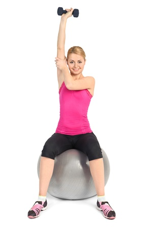bent over: Young woman doing Seated Dumbbell One Arm Triceps Extensions on Fitness Ball, phase 2 of 2. Stock Photo