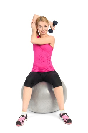 bent over: Young woman doing Seated Dumbbell One Arm Triceps Extensions on Fitness Ball, phase 1 of 2.