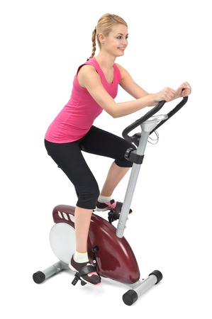 young woman doing indoor biking exercise, on white background Standard-Bild