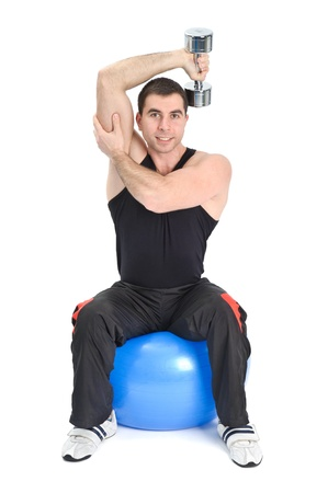 triceps: Young man doing Seated Dumbbell One Arm Triceps Extensions on Fitnes Ball, phase 1 of 2.