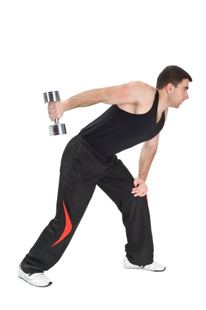 Young man doing Standing Dumbbell One Arm Triceps Extensions on Fitnes Ball, phase 2 of 2. Stock Photo - 12534062
