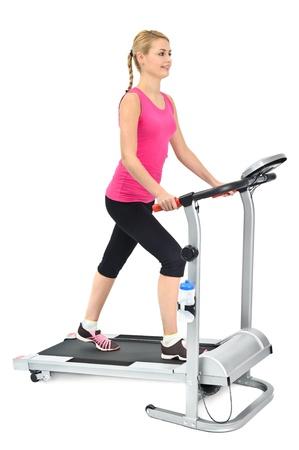 jonge vrouw doet oefeningen op de loopband, op een witte achtergrond Stockfoto