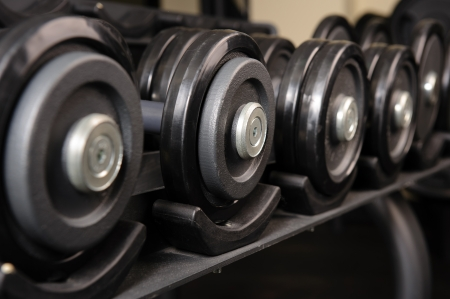 Row of black barbells in the rack, ready for workout