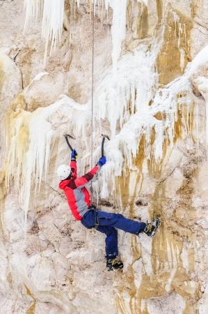 ice axe: Young man climbing the ice using ice axe