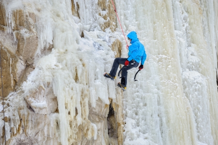 ice axe: Young man climbing the ice using ice axe, motion blur Stock Photo