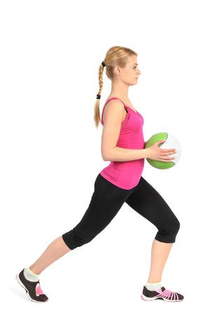 lunges: Chica joven que hace estocadas ejercicio con bal�n medicinal