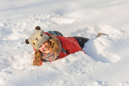 somersault: beautiful young girl in funny hat playing in fresh snow